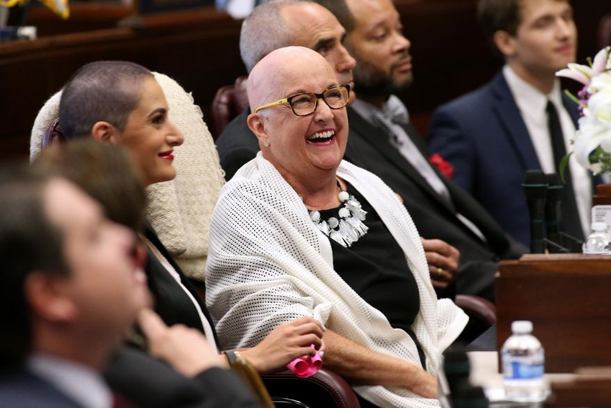 FILE - In this Wednesday, April 8, 2015, file photo, Nevada Sen. Debbie Smith, D-Sparks, center, is recognized on the Senate floor at the Legislative Building in Carson City, Nev. Smith was busy preparing for the 2015 legislative session 10 months ago when it was discovered that she had a cancerous brain tumor. After a successful surgery, she was back in the legislature for the session's final six weeks. (AP Photo/Cathleen Allison, File)