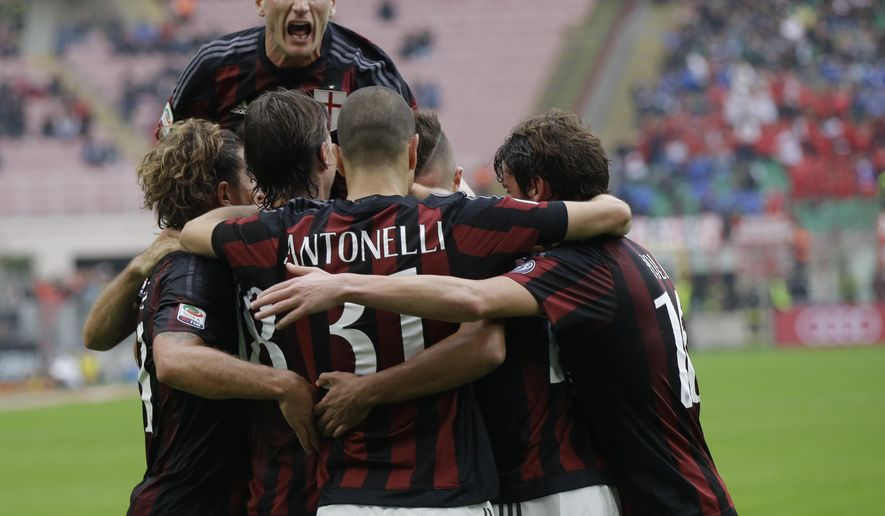 AC Milan 's Ignazio Abate jumps over his teammates in celebration after Carlos Bacca scored the opening goal during a Serie A soccer match between AC Milan and Sassuolo, at the San Siro stadium in Milan, Italy, Sunday, Oct. 25, 2015. (AP Photo/Luca Bruno)