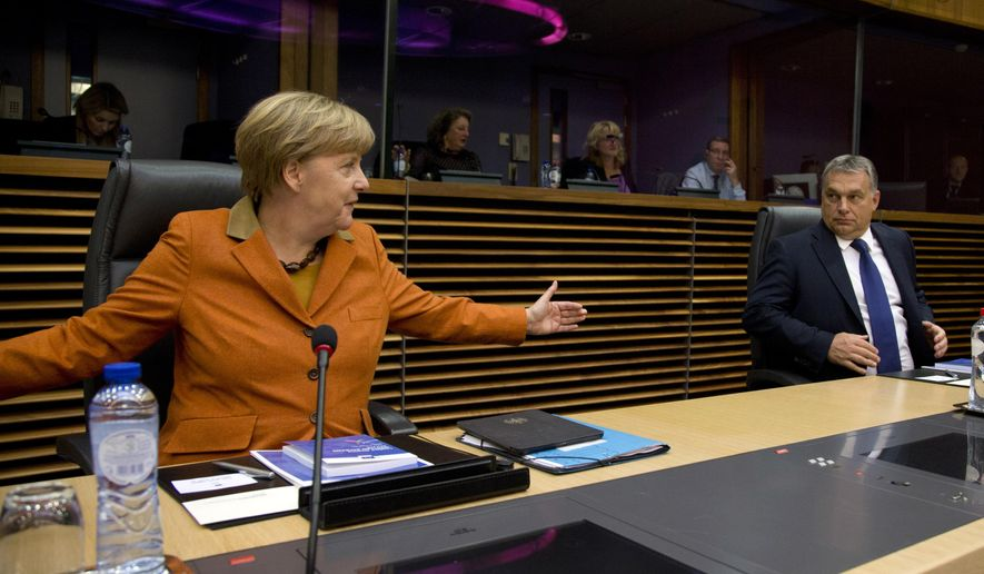 German Chancellor Angela Merkel, left, gestures regarding the space between chairs as she speaks with Hungarian Prime Minister Viktor Orban prior to the start of a round table meeting during an EU summit at EU headquarters in Brussels on Sunday, Oct. 25, 2015. EU leaders meet on Sunday to discuss refugee flows along the Western Balkans route. (AP Photo/Virginia Mayo)