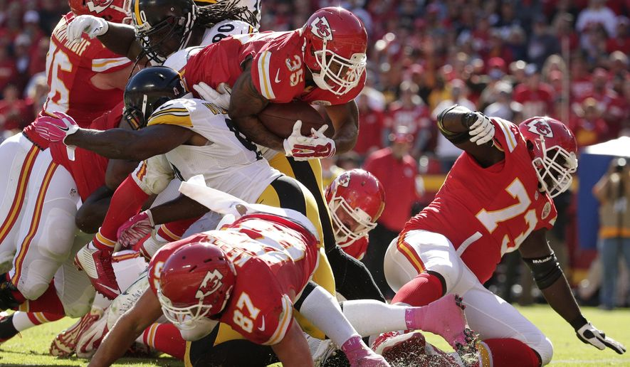 Kansas City Chiefs running back Charcandrick West (35) leaps over players to score a touchdown during the second half of an NFL football game against the Pittsburgh Steelers in Kansas City, Mo., Sunday, Oct. 25, 2015. (AP Photo/Charlie Riedel)