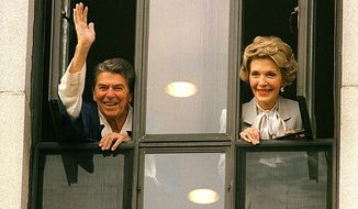 Ronald Reagan and wife Nancy appear at a hospital window to reassure the nation the president was on the mend following a 1981 assassination attempt (AP Photo)