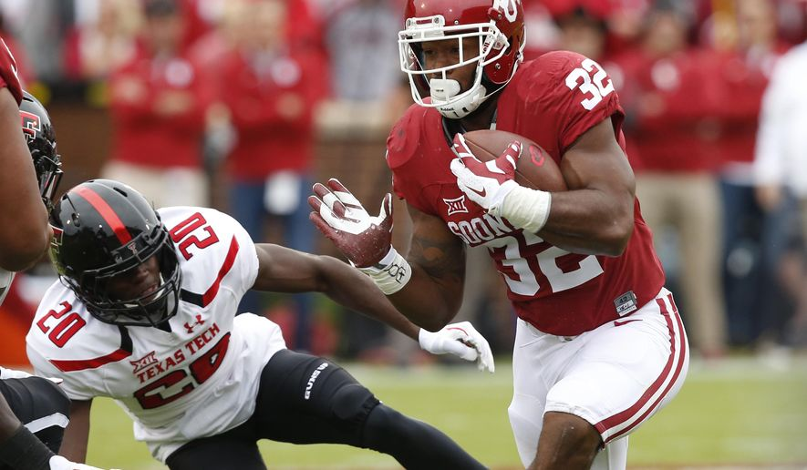 Oklahoma running back Samaje Perine (32) carries past Texas Tech defensive back Tevin Madison (20) in the first quarter of an NCAA college football game in Norman, Okla., Saturday, Oct. 24, 2015. Oklahoma won 63-27. (AP Photo/Sue Ogrocki)