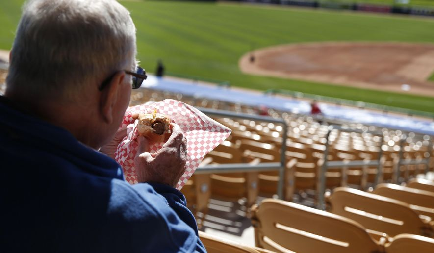 """FILE - In this March 4, 2015 file photo, a fan eats a hot dog before a spring training exhibition baseball game between the Chicago White Sox and the Los Angeles Dodgers, in Phoenix. On the eve of the World Series, where hot dogs are a staple in the stands, the World Health Organization on Monday, Oct. 26, 2015 labeled the all-American wiener, bacon and other processed meats as being """"carcinogenic to humans."""" (AP Photo/John Locher, File)"""