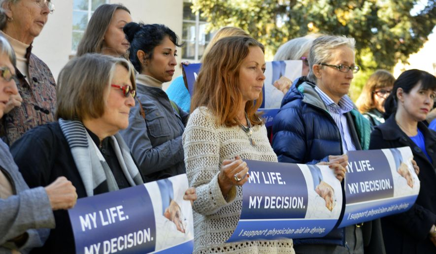 Right to die advocates rally on Monday, Oct. 26, 2015, outside the New Mexico Supreme Court in Santa Fe after a lawyer asked justices to allow terminally-ill patients to end their lives. Justices heard oral arguments Monday in a case that could overturn the state's assisted suicide law which allows prosecutors to criminally charge doctors who help terminally-ill patients end their lives. (AP Photo/Russell Contreras)