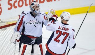 Washington Capitals goalie Braden Holtby, left, and teammate Karl Alzner celebrate the team's 3-2 win over the Vancouver Canucks in an NHL hockey game in Vancouver, British Columbia, on Thursday, Oct. 22, 2015. (Darryl Dyck/The Canadian Press via AP)