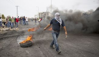 Palestinians burn tires during clashes with Israeli troops near Ramallah, West Bank, Friday, Oct. 23, 2015. (AP Photo/Majdi Mohammed) ** FILE **