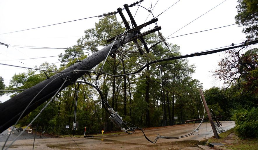 A power line pole is bent over near Pierremont Rd. in Shreveport, La., Monday, Oct. 26, 2015. A massive tree has taken out eight power poles, and more than 160 customers are without power there, with the road closed between Gilbert Drive and Creswell Road. (Henrietta Wildsmith/Shreveport Times via AP)