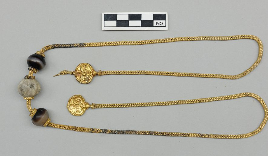 This picture provided by Greece's Culture Ministry on Monday, Oct. 26, 2015, shows - after cleaning - a long gold chain, decorated with semi-precious stones and hammered-gold plant decorations, found in a 3,500-year-old warrior's tomb. Authorities say a 3,500-year-old, treasure-filled grave of a warrior has been discovered near an ancient palace in southern Greece. The Culture Ministry says the grave is the most spectacular discovery of its kind from the Mycenaean era in more than six decades. It contained about 1,400 artefacts, including gold and silver jewelry, cups, bronze vases, engraved gemstones and an ornate ivory-and gilt-hilted sword. (Greek Culture Ministry via AP)