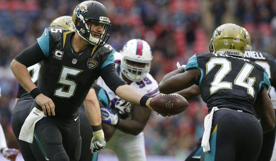 Jacksonville Jaguars quarterback Blake Bortles (5), left, hands off to running back T.J. Yeldon (24)  during the NFL game between Buffalo Bills and Jacksonville Jaguars at Wembley Stadium in London,  Sunday, Oct. 25, 2015. (AP Photo/Matt Dunham)
