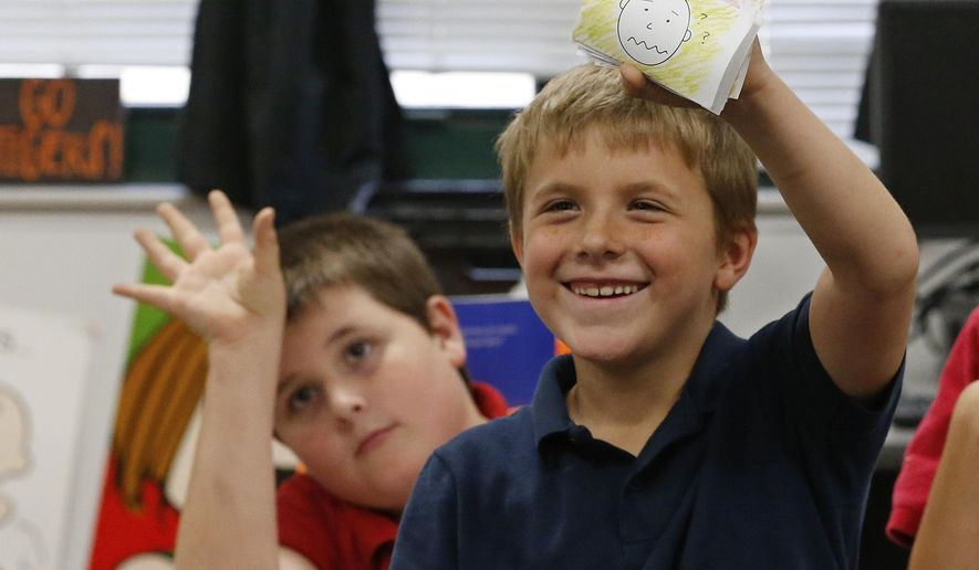 Junior Bowersock, 8, holds up a photo card that expresses his feelings during a New Hope after-school program at Mark Twain Elementary School, Wednesday, Oct. 21, 2015, in Tulsa, Okla. At left is his brother, Bryan, 11. New Hope Oklahoma offers after-school programs, weekend retreats and overnight summer camps that annually serve about 500 children who have a parent in prison. (AP Photo/Sue Ogrocki)