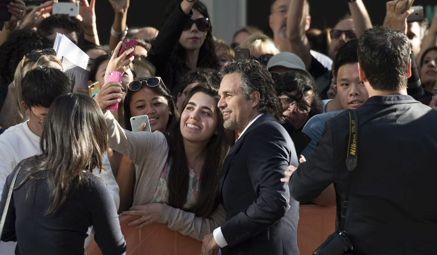"FILE - In this Sept. 14, 2015, file photo, actor Mark Ruffalo poses for a selfie with a fan on the red carpet for the film ""Spotlight"" during the 2015 Toronto International Film Festival. The film, being released in theaters on Nov. 6, 2015, tells the story of how The Boston Globe exposed the Roman Catholic Church's clergy sex abuse scandal. (Darren Calabrese/The Canadian Press via AP, File)"