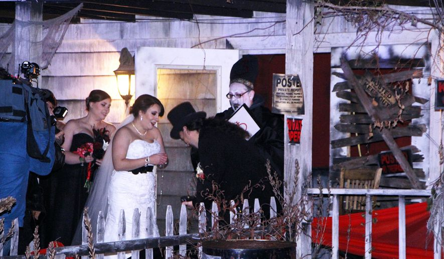 """In this photo provided by Spooky World Presents Nightmare New England, Melissa Cote and Tom Cowen, who both work at Spooky World Presents Nightmare New England in Litchfield, N.H., were married the night of Monday, Oct. 26, 2015, in front of the attraction's haunted house. During the ceremony, the justice of the peace encouraged them to """"haunt and howl at the moon together as long as you shall live,"""" and """"to have and to hold from this night on, in madness and in haunting fun.""""  (Spooky World Presents Nightmare New England via AP)"""