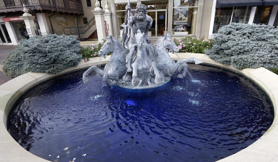 A fountain of Neptune and his Trident is dyed blue in Kansas City, Mo., Monday, Oct. 26, 2015. The color honors the Kansas City Royals second consecutive appearance in the World Series. (AP Photo/Orlin Wagner)