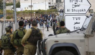 """Israeli soldiers and Palestinians stand at the scene of a stabbing attack, in the West Bank settlement of Kiryat Arba, Monday, Oct. 26, 2015. The Israeli military said a Palestinian stabbed an Israeli in the West Bank before being shot and killed. According to the military, the Israeli was stabbed in the neck Monday and """"severely wounded"""" near the city of Hebron. (AP Photo/Wisam Hashlamoun)"""