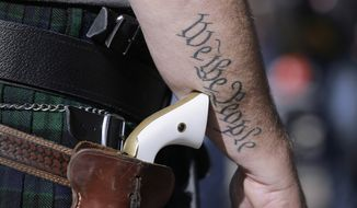 Scott Smith, a supporter of open carry gun laws, wears a pistol as he prepares for a rally at the Capitol on Jan. 26, 2015, in Austin, Texas. (Associated Press) ** FILE **
