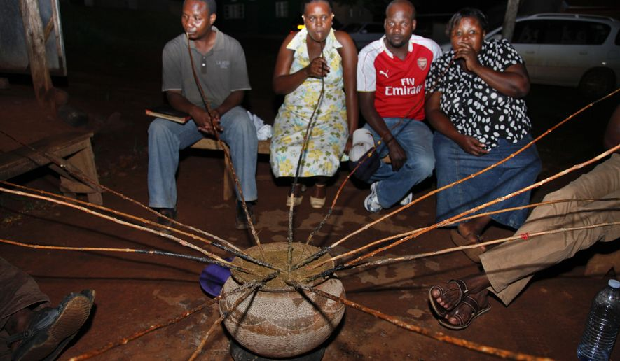 """In this photo taken Sunday, Oct. 18, 2015, Ugandans drink a local brew known as """"malwa"""" at the Charismatic Club in the Kitintale district of Kampala, Uganda. With beer sales slowing in North America and Europe, Anheuser-Busch InBev has agreed to pay more than $100 billion for rival SABMiller, in large part to tap burgeoning growth in Africa, where many people still buy their beer from small neighborhood brewers. (AP Photo/Stephen Wandera)"""