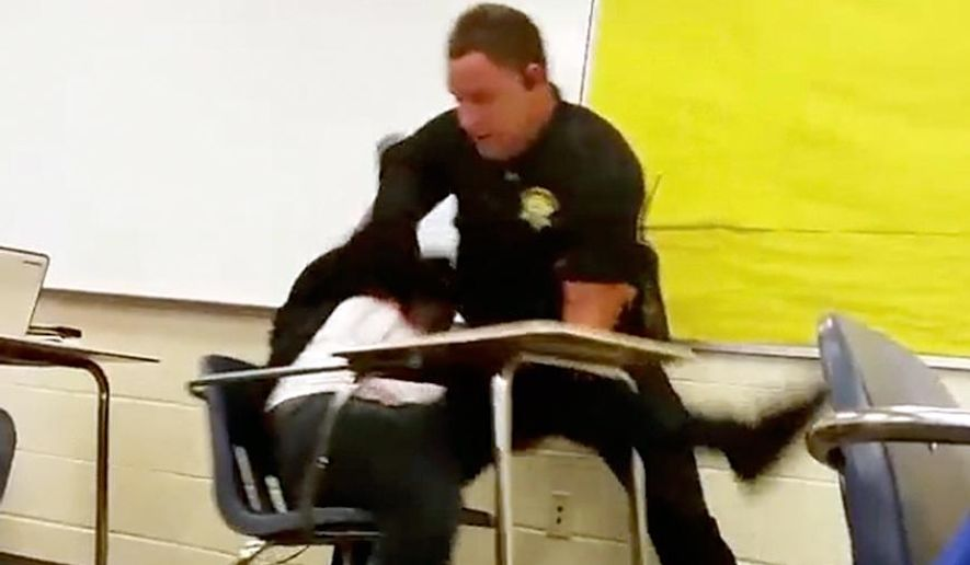 In this Monday, Oct, 26, 2015, photo made from video taken by a Spring Valley High School student, Senior Deputy Ben Fields tries to forcibly remove a student who refused to leave her high school math class, in Columbia S.C. The Justice Department opened a civil rights investigation Tuesday after Fields flipped the student backward in her desk and tossed her across the floor. (Associated Press)