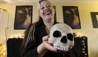 Lilith Starr, chapter head of The Satanic Temple of Seattle, holds a plastic skull while being photographed in her home Wednesday, Oct. 28, 2015, in Seattle. At the invitation of the Bremerton High School senior class president, Starr says that her group of self-described Satanists will attend the school's football game Thursday to protest a decision by a Christian coach to continue praying at the 50-yard line after games. (AP Photo/Elaine Thompson)