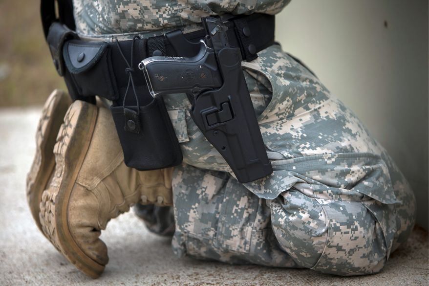 A member of the 139th Military Police Company kneels with his holstered 9mm Beretta M9 during a qualifying exercise at a small arms range, Tuesday, Sept. 29, 2015, in Fort Stewart, Ga. The Army wants to replace its M9, a 9mm semi-automatic handgun adopted during the Cold War. The new gun also will replace the smaller M11.  (AP Photo/Stephen B. Morton)