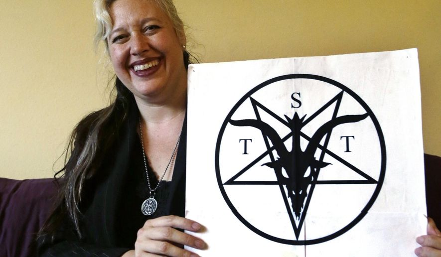 Lilith Starr, chapter head of The Satanic Temple of Seattle, holds her organization's poster while being photographed in her home Wednesday, Oct. 28, 2015, in Seattle. At the invitation of the Bremerton High School senior class president, Starr says that her group of self-described Satanists will attend the school's football game Thursday to protest a decision by a Christian coach to continue praying at the 50-yard line after games. (AP Photo/Elaine Thompson)