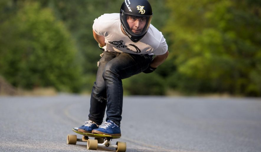 ADVANCE FOR SATURDAY, OCT. 31, 2015- In this photo taken on Aug. 20, 2015, Chris Burton races down Fernan Lake Road on a specially designed skateboard at speeds topping 40 miles per hour, in Coeur d'Alene, Idaho.  (Jake Parrish /Coeur D'Alene Press via AP) MANDATORY CREDIT