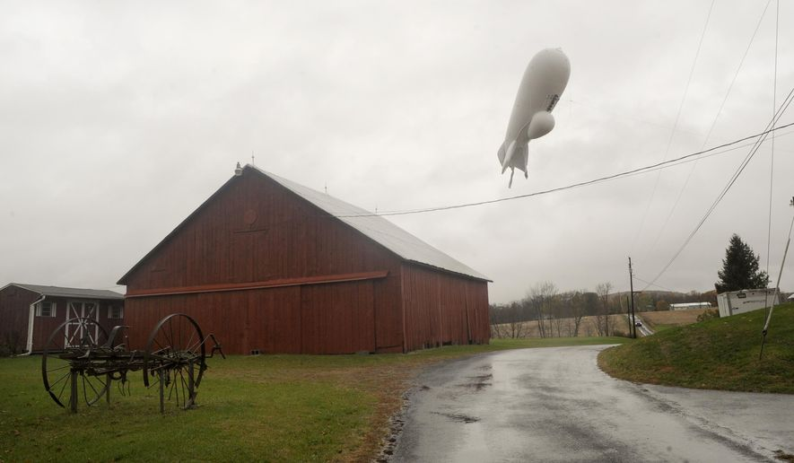 An unmanned Army surveillance blimp floats through the air while dragging a tether line south of Millville, Pa., Wednesday, Oct. 28, 2015. The bulbous, 240-foot helium-filled blimp came down near Muncy, a small town about 80 miles north of Harrisburg. The North American Aerospace Defense Command in Colorado said the blimp detached from its station at the military's Aberdeen Proving Ground in Maryland.  (Jimmy May/Bloomsburg Press Enterprise via AP)