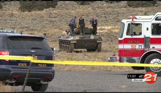 This Tuesday, Oct. 27, 2015, image made from video by KTVZ-TV shows investigators inspecting the scene of an explosion inside a World War II-era tank at a public firing range that left two people dead near Bend, Ore. (Steve Kaufmann/KTVZ-TV via AP)