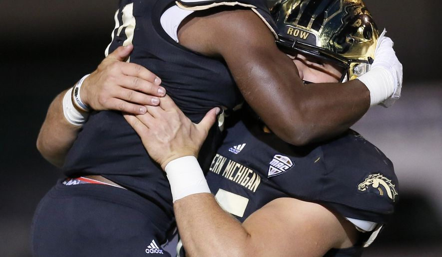 Western Michigan's Jamauri Bogan celebrates with Dan Buschman, right, during the first half of an NCAA football game against Eastern Michigan, Thursday, Oct. 29, 2015, in Ypsilanti, Mich. (AP Photo/Duane Burleson)