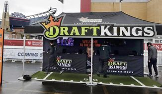 Workers set up a DraftKings promotions tent in the parking lot of Gillette Stadium, in Foxborough, Mass., before an NFL football game between the New England Patriots and New York Jets. The Massachusetts Gaming Commission meets Thursday, Oct. 29, 2015, to discuss regulating daily fantasy sports contests run by Boston-based DraftKings and other companies that have exploded in popularity in recent years. (AP Photo/Charles Krupa)