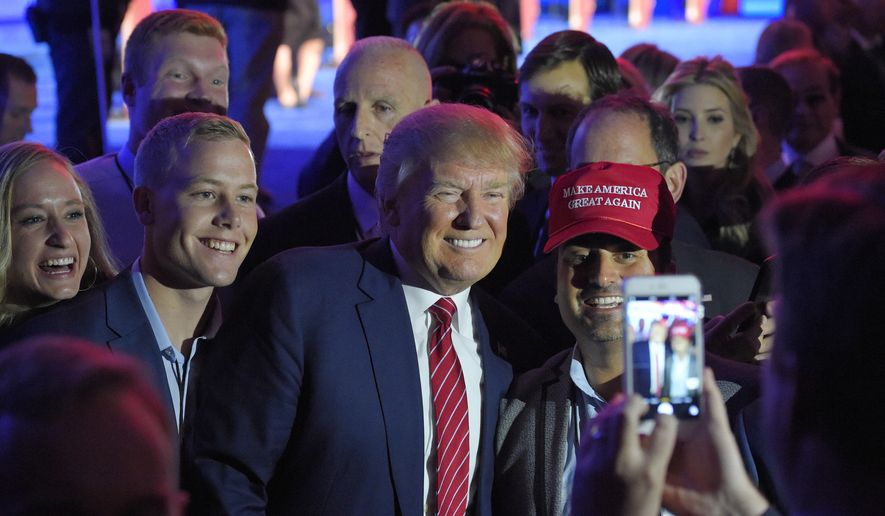 Donald Trump, center, poses for a photo with Denver attorney Gabriel Schwartz (with hat) and others following the CNBC Republican presidential debate at the University of Colorado, Wednesday, Oct. 28, 2015, in Boulder, Colo. (AP Photo/Mark J. Terrill)