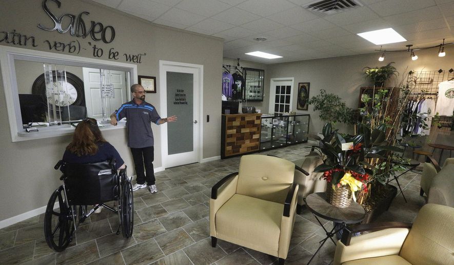 In this Oct. 20, 2015 photo, Shamay Flaharty, of Lewiston, Ill., who has multiple sclerosis and is hoping cannabis will help ease her pain and headaches, meets with Eric Sweatt, partner and manager of Salveo Health and Wellness, a licensed medical cannabis dispensary, in Canton, Ill. Illinois will begin its first medical marijuana sales within the next two weeks. (AP Photo/Seth Perlman)