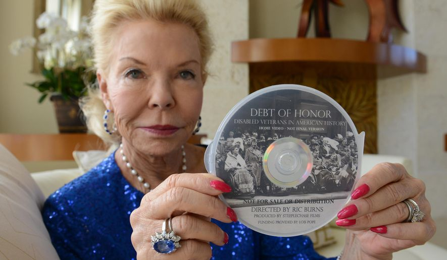 """ADVANCE FOR USE SATURDAY, OCT. 31 - In this photo taken Thursday, Oct. 22, 2015, Palm Beach County philanthropist Lois Pope poses at her home in Boynton Beach, Fla., with a DVD copy of a PBS documentary about disabled military veterans she is helping present.  """"Debt of Honor: Disabled Veterans in American History"""", funded by Pope and directed by six-time Emmy Award-winning director Ric Burns, airs Nov. 10 nationwide.. (Jim Rassol/South Florida Sun-Sentinel via AP) NO SALES, TV OUT, MAGS OUT; MANDATORY CREDIT."""