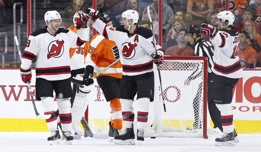 New Jersey Devils' Travis Zajac, center, celebrates his goal on Philadelphia Flyers' Steve Mason, left center, with Jiri Tlusty, left, of Czech Republic and Jacob Josefson, right  during the second period of a hockey game, Thursday, Oct. 29, 2015, in Philadelphia. (AP Photo/Chris Szagola)