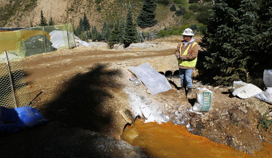 """FILE - In this Aug. 14, 2015 file photo, an Environmental Protection Agency contractor keeps a bag of lime on hand to correct the PH of mine wastewater flowing into a series of sediment retention ponds, part of danger mitigation in the aftermath of the blowout at the site of the Gold King Mine outside Silverton, Colo. Congressional Republicans on Thursday, Oct. 29, 2015, revived """"Good Samaritan"""" legislation designed to encourage companies and nonprofits to clean up abandoned mines by protecting them from liability for environmental accidents in the future. (AP Photo/Brennan Linsley, file)"""