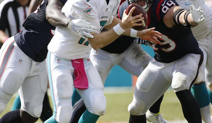 Houston Texans outside linebacker Jadeveon Clowney (90) sacks Miami Dolphins quarterback Ryan Tannehill (17) during the first half of an NFL football game, Sunday, Oct. 25, 2015 in Miami Gardens, Fla. Houston Texans defensive end J.J. Watt (99) is to the right. (AP Photo/Wilfredo Lee)