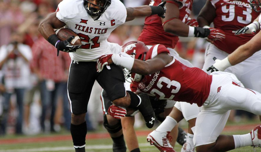 FILE - In this Sept. 19, 2015, file photo, Arkansas' Dre Greenlaw (23) grabs Texas Tech's DeAndre Washington (21) during the first half of an NCAA college football game in Fayetteville, Ark. After entering foster care at 8, Greenlaw was adopted by one of his high school coaches and has quickly become one of the top newcomers in the Southeastern Conference this season. (AP Photo/Samantha Baker, File)