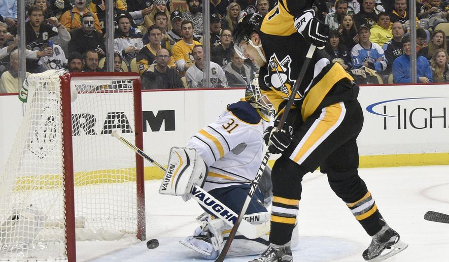 Pittsburgh Penguins defenseman Ben Lovejoy (12) scores against Buffalo Sabres goalie Chad Johnson (31) during the second period of an NHL hockey game on Thursday, Oct. 29, 2015, in Pittsburgh. (AP Photo/Don Wright)