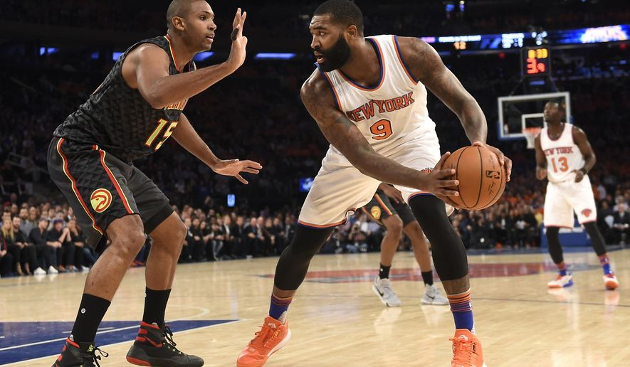 New York Knicks forward Kyle O'Quinn (9) tries to move the ball around Atlanta Hawks forward Al Horford (15) during the first half of an NBA basketball game on Thursday, Oct. 29, 2015, in New York. (AP Photo/Kathy Kmonicek)
