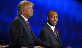 Ben Carson (right) watches Donald Trump during the CNBC Republican presidential debate at the University of Colorado in Boulder on Oct. 28, 2015. (Associated Press) **FILE**