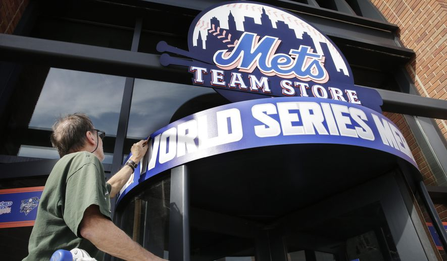 Joel Silva smooths a new World Series  sign at Citi Field in New York, Thursday, Oct. 29,  2015. The New York Mets are to face the Kansas City Royals in Game 3 of the World Series at the stadium on Friday. (AP Photo/Peter Morgan)