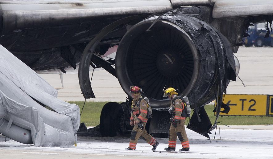 Firefighters walk past a burned out engine of a Dynamic Airways Boeing 767, Thursday, Oct. 29, 2015, at Fort Lauderdale/Hollywood International Airport in Dania Beach, Fla. The passenger plane's engine caught fire Thursday as it prepared for takeoff, and passengers had to quickly evacuate on the runway using emergency slides, officials said. The plane was headed to Caracas, Ven. (AP Photo/Wilfredo Lee)