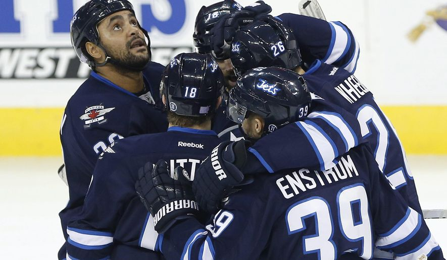 Winnipeg Jets' Dustin Byfuglien (33) looks up at the reply as his teammates celebrate Blake Wheeler's (26) goal against the Chicago Blackhawks during first period NHL action in Winnipeg on Thursday, Oct. 29, 2015.  (John Woods/The Canadian Press via AP)