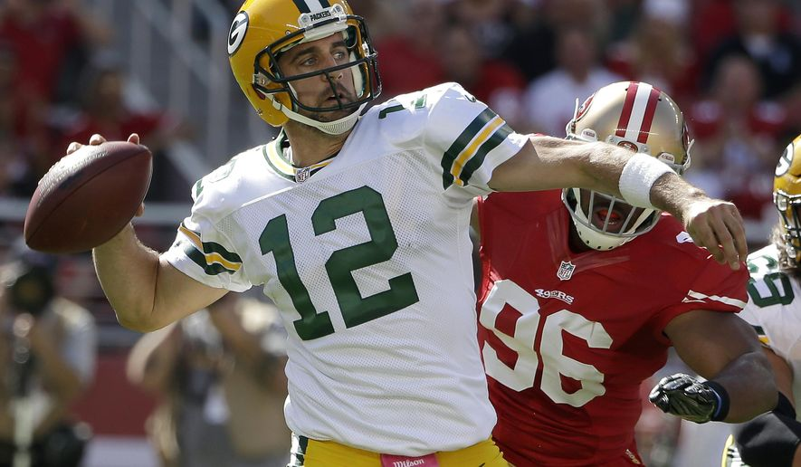 FILE - In this Oct. 4, 2015, file photo, Green Bay Packers quarterback Aaron Rodgers (12) passes as San Francisco 49ers linebacker Corey Lemonier (96) applies pressure during the first half of an NFL football game in Santa Clara, Calif. Usually the hype machine points toward February and the Super Bowl when two runaway division leaders meet. Yet when the Packers visit the Denver Broncos, both 6-0, on Sunday, Nov. 1, 2015, there is not much Super Bowl preview talk. (AP Photo/Marcio Jose Sanchez, File)