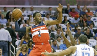 John Wall (2) passes the ball over Orlando Magic forward Tobias Harris during the first half of an NBA basketball game, Wednesday, Oct. 28, 2015, in Orlando, Fla. (AP Photo/John Raoux)