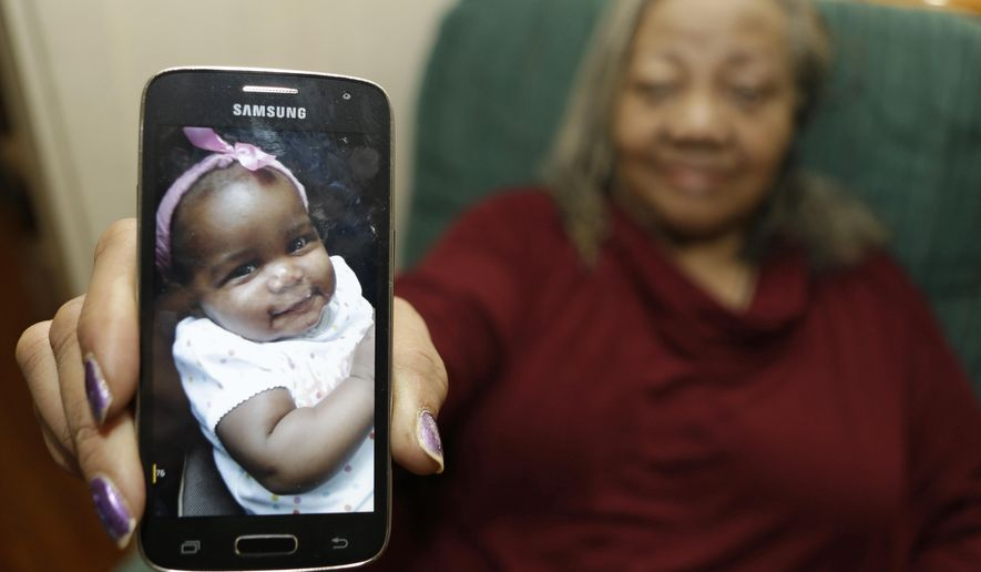In this Wednesday, Oct. 28, 2015, photo, Beatrice Wakefield holds up a picture of her granddaughter Aavielle at her home in Cleveland. Wakefield was in a car with her daughter-in-law, her granddaughter Aavielle Wakefield and another child on the way to the grocery store when someone began firing at the vehicle, striking it numerous times. Aavielle, 5-months-old, sitting in her car seat, was fatally struck in the torso. No one else was injured. The killing remains unsolved. (AP Photo/Tony Dejak)