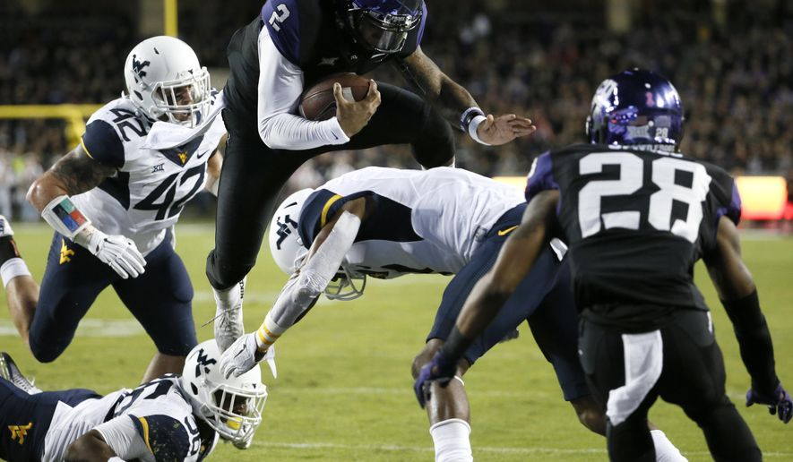 TCU quarterback Trevone Boykin (2) leaps over West Virginia cornerback Daryl Worley into the end zone for a touchdown after getting by West Virginia's Jared Barber (42) and Shaq Petteway, bottom, in the first half of an NCAA college football game Thursday, Oct. 29, 2015, in Fort Worth, Texas. TCU's Tony James watches on the play. (AP Photo/Tony Gutierrez)