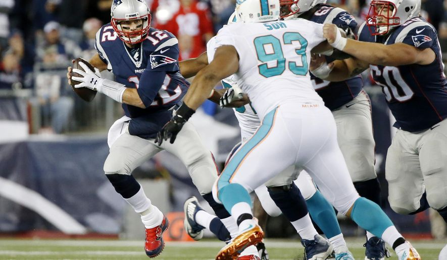 New England Patriots quarterback Tom Brady (12) scrambles away from Miami Dolphins defensive tackle Ndamukong Suh (93) in the first half of an NFL football game, Thursday, Oct. 29, 2015, in Foxborough, Mass. (AP Photo/Michael Dwyer)