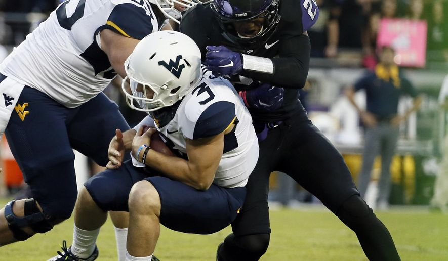 West Virginia quarterback Skyler Howard (3) is stopped by linebacker Montrel Wilson (20) after a short run in the first half of an NCAA college football game Thursday, Oct. 29, 2015, in Fort Worth, Texas. (AP Photo/Tony Gutierrez)