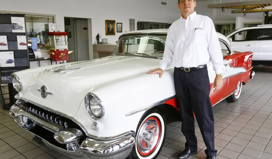 In this photo taken Wednesday, Oct. 28, 2015, Reliable Cadillac GMC owner Bill Porter stands beside a 1955 Oldsmobile 88 Holiday Coupe on display in the dealership's showroom in Selma, Ala. The car was sold by Reliable in 1955, and Porter recently repurchased the pristine vehicle from the owner. (AP Photo/Alaina Denean Deshazo, The Selma Times-Journal)