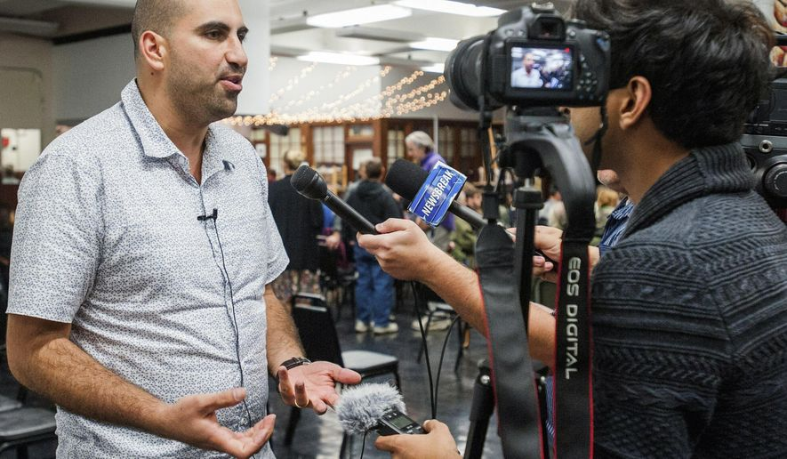 In this Oct. 13, 2015 photo, professor Steven Salaita is interviewed before his talk at the Independent Media Center in Urbana, Ill. University of Illinois Chancellor Barbara Wilson told faculty members at a town hall on Monday, Oct. 26, 2015, that the school hopes to have the lawsuit settled soon that was brought by Salaita, who lost his job offer over a series of profane anti-Israel Twitter messages. (Robin Scholz/The News-Gazette via AP) MANDATORY CREDIT